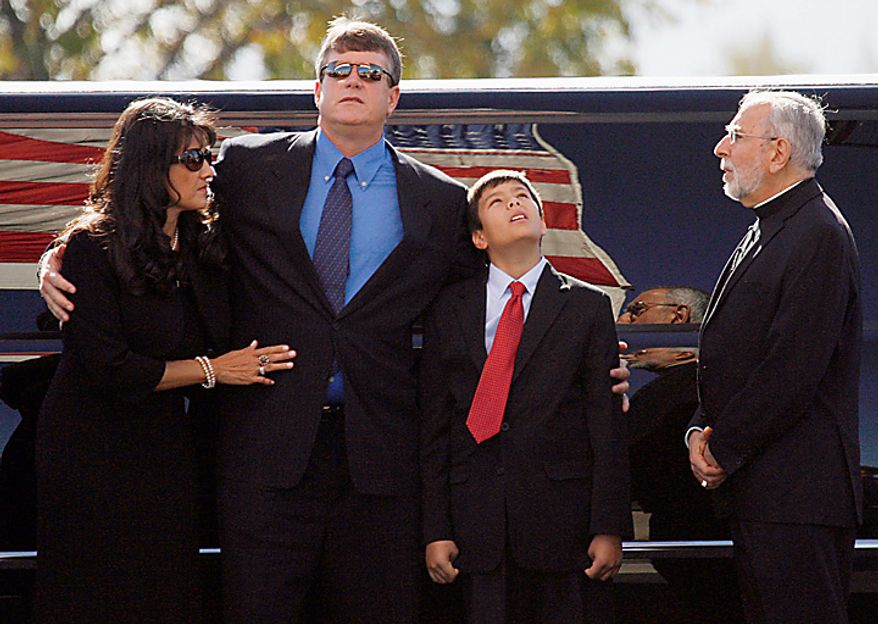 Roxanna and John Green, the mother and father of Christina Green, stand with their son Dallas as they arrive for Christina's funeral at the St. Elizabeth Ann Seton Church on Thursday, Jan. 13, 2011, in Tucson, Ariz. Green was the youngest victim of Saturday's shooting in Tucson. (AP Photo/Mamta Popat, Pool)