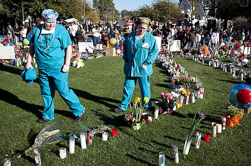 University Medical Center nurses visit the makeshift memorial to Rep. Gabrielle Giffords and other victims of Saturday's shootings, Wednesday, Jan .12, 2011, in front of the Tucson, Ariz. hospital. (AP Photo/The Arizona Republic, Mark Henle)