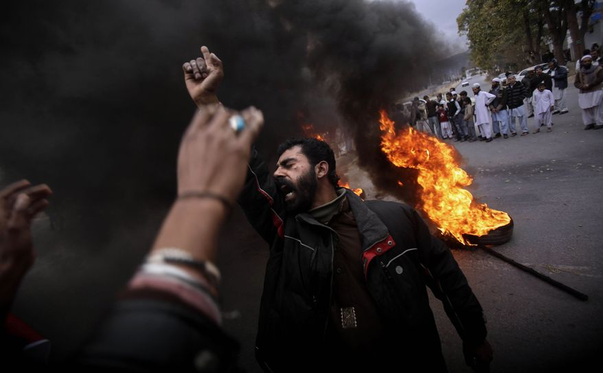 Pakistani demonstrators shout slogans against recent statements by Pope Benedict XVI about Pakistan's blasphemy laws, next to burning tires during a rally in Islamabad, Pakistan, Friday, Jan. 14, 2011. (AP Photo/Muhammed Muheisen)