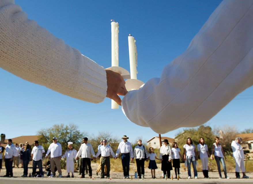 Several hundred people, many dressed in white T-shirts, stood silently along a road near St. Elizabeth Ann Seton Parish, the site of Christina Taylor Green's funeral, in Tucson, Ariz., on Thursday. (Associated Press)