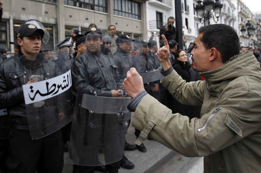 A protester faces police officers as he chants slogans against President Zine El Abidine Ben Ali in Tunis, Friday, Jan. 14, 2011. Thousands of angry demonstrators marched through Tunisia's capital Friday, demanding the resignation of the country's autocratic leader a day after he appeared on TV to try to stop deadly riots that have swept the North African nation. (AP Photo/Christophe Ena)