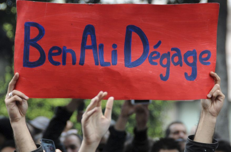 """Protesters hold a banner reading """"Ben Ali get out"""", calling for the resignation of Tunisia's President Zine El Abidine Ben Ali, in the capital, Tunis, Friday, Jan. 14,2011. (AP Photo)"""
