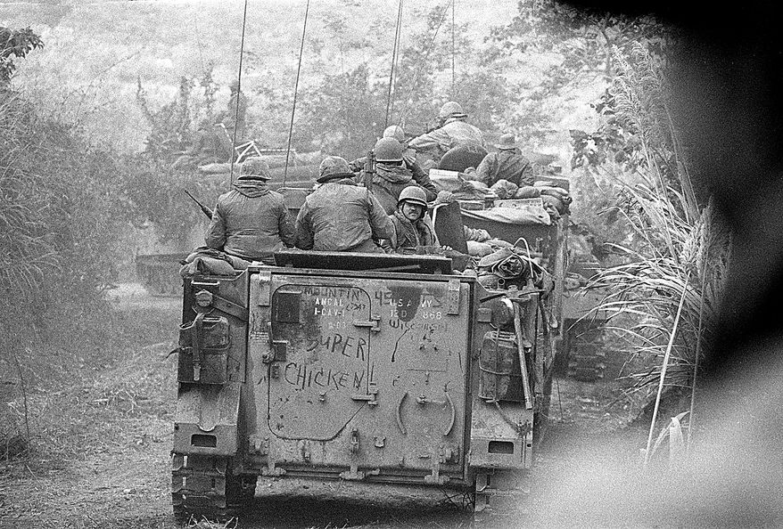 Soldiers of the Americal Divison ride on armored personnel carriers toward Lang Vel Special Forces camp, half a mile from the Laotian border during the Vietnam War, 1971.  The Americans had to clear Route 9 to the Laotian border for the South Vietnamese invasion into Laos.  (AP Photo/Henri Huet)