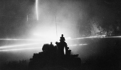 Soldiers of the U.S. 11th Armored Cavalry Regiment are silhouetted atop their tank by the glare of tracer bullets in Cambodia, July 6, 1970.  In an exercise known as Mad Minute, they spray the area around them, possibly infiltrated by enemy patrols, before they move on.  (AP Photo/Henri Huet)