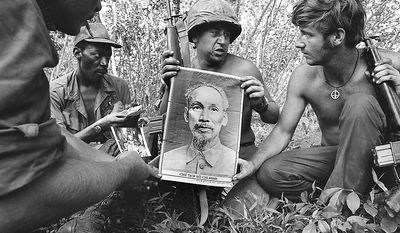 U.S. soldiers hold a large cloth portrait of late North Vietnamese President Ho Chi Minh, found during a search of the Mimot rubber plantation about eight miles inside Cambodia, in early May 1970. (AP Photo/Henri Huet)