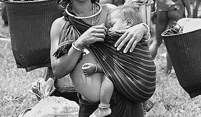 A woman of the Montagnard tribe cradles a baby as members of the tribe are relocated from Bu Lack village in September 1968. The Montagnards were being transported to a refugee camp. (AP Photo/Henri Huet)