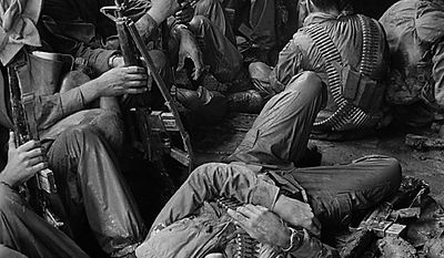 U.S. soldiers of the 9th Infantry Division relax on the long boat trip back to their base camp after a day trudging through the coconut groves of Kien Hoa province in the Mekong Delta during the Vietnam War, 1969.  (AP Photo/Henri Huet)