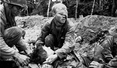First Cavalry Division Medic Thomas Cole, from Richmond, Va., wearing a bandage over the left side of his face, tends to an unidentified soldier in a trench during battle in the Vietnam War, 1966.  The trench had been the first line of Viet Cong and North Vietnamese defense until it was taken by American forces.  (AP Photo/Henri Huet)