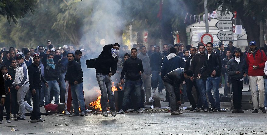 Demontrators throw rocks towards police during clashes in Tunis, Friday, Jan. 14, 2011. Tunisia's president declared a state of emergency and announced that he would fire his government as violent protests escalated Friday, with gunfire echoing in the North African country's usually calm capital and police lobbing tear gas at protesters. (AP Photo/Christophe Ena)