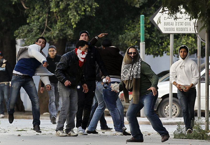 Demonstrators  clash with police after a demonstration in Tunis, Friday, Jan. 14, 2011. Tunisia's president declared a state of emergency and announced that he would fire his government as violent protests escalated Friday, with gunfire echoing in the North African country's usually calm capital and police lobbing tear gas at protesters. (AP Photo/Christophe Ena)