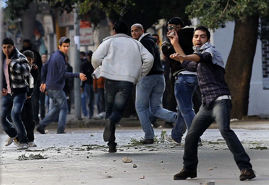 Demonstrators throw stones at police during clashes in Tunis, Friday, Jan. 14, 2011. Tunisia's president declared a state of emergency and announced that he would fire his government as violent protests escalated Friday, with gunfire echoing in the North African country's usually calm capital and police lobbing tear gas at protesters. (AP Photo/Christophe Ena)