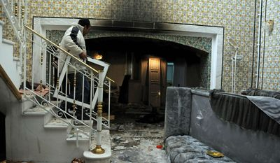 A man carries goods from the house of Belhassen Trabelsi, the brother of the former president's wife, Leila Ben Ali, in Sokra, 16 kms (10 miles) from Tunis, Saturday, Jan. 15, 2011. The Tunisian capital's main train station has been burned to the ground, and many shops have been sacked and looted in violence that came after the North African nation's president fled the country. (AP Photo/Hassene Dridi)