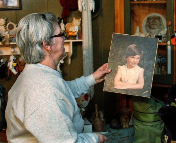 """Janice McKinney places a portrait of her daughter, Cherrie Mahan, that was made a few years before the 8-year-old went missing back in 1985, back onto the cabinet where she keeps it in her home in Saxonburg, Pa. State police say someone has provided """"potentially crucial"""" information that could help them solve the case of the Pennsylvania girl missing for almost 26 years. (Associated Press)"""
