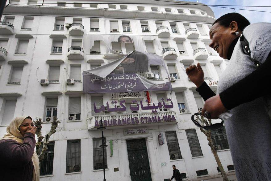 Women smile as they walk past a torn poster with a photo of former Tunisian President Zine El Abidine Ben Ali in the center of Tunis, the Tunisian capital, on Sunday, Jan. 16. 2011. (AP Photo/Christophe Ena)