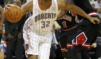In this photo taken Jan. 12, 2011, Charlotte Bobcats' Boris Diaw (32) shoots as Chicago Bulls' Carlos Boozer (5) and Derrick Rose (1) defend in the second half of the Bobcats' 96-91 win in an NBA basketball game in Charlotte, N.C. The Bobcats nearly traded Diaw twice in the offseason, yet he insists it doesn't bother him. Teammate Gerald Wallace says it's sometimes maddening how he never gets upset at anything. Despite his quirks, the power forward is a key reason Charlotte is surging under new coach Paul Silas. (AP Photo/Chuck Burton)