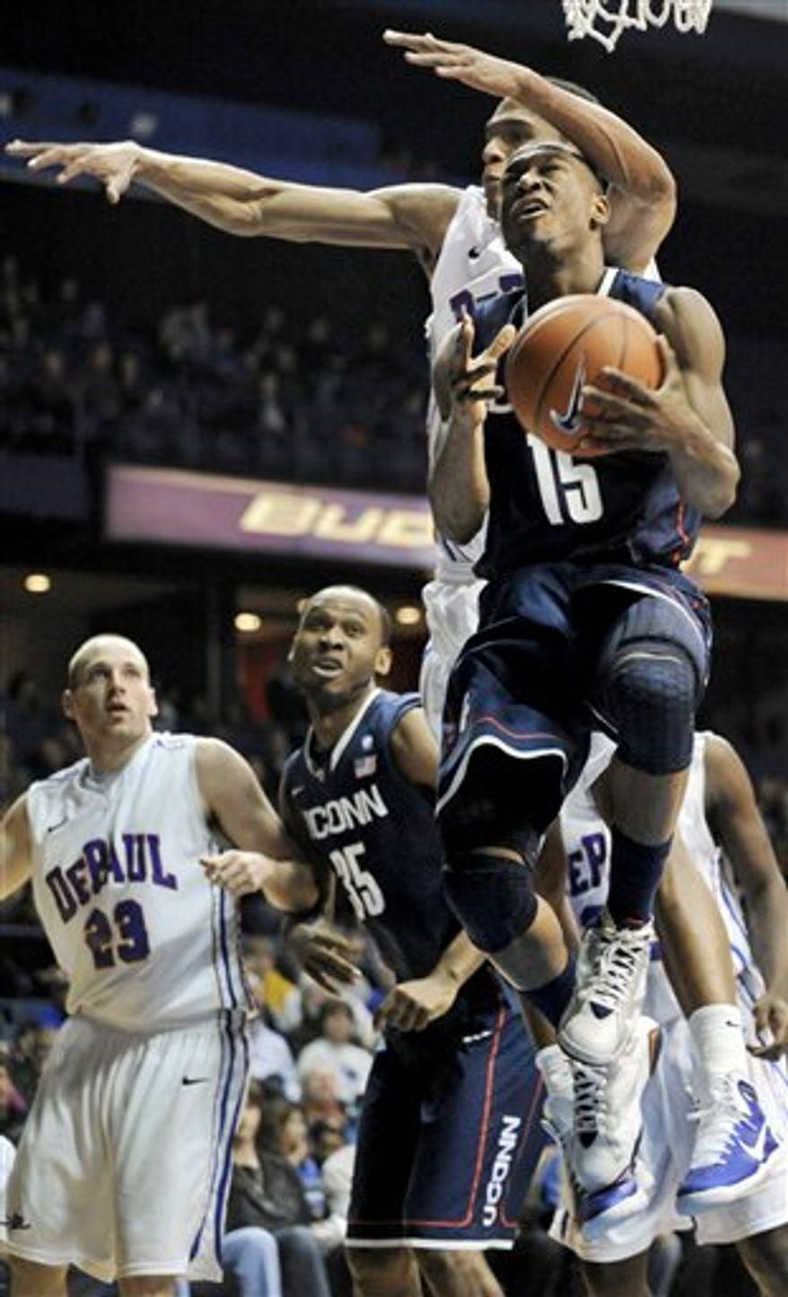 Connecticut's Kemba Walker, foreground, goes up for a shot against DePaul's Cleveland Melvin in the second half during an NCAA college basketball game in Rosemont, Ill., Saturday, Jan. 15, 2011. Connecticut won 82-62. (AP Photo/Paul Beaty)