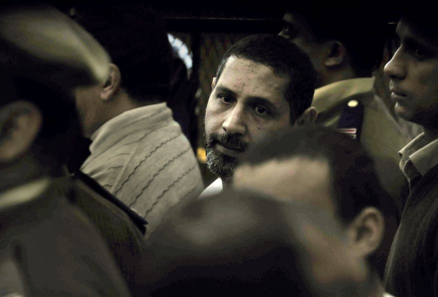 ** FILE ** Mohammed Ahmed Hassanein, also known by the alias Hammam al-Kamouni, who was one of three suspects charged in a Coptic Christmas Eve drive-by shooting on Jan. 6, 2010, in the southern Egyptian town of Nag Hamadi that killed seven people, looks on during his trial in Qena, Egypt, on Saturday, Feb. 13, 2010. The court on Sunday, Jan. 16, 2011, convicted and sentenced to death al-Kamouni for his part in the shooting, judicial officials said. (AP Photo/Mohammed Ahmed, File)