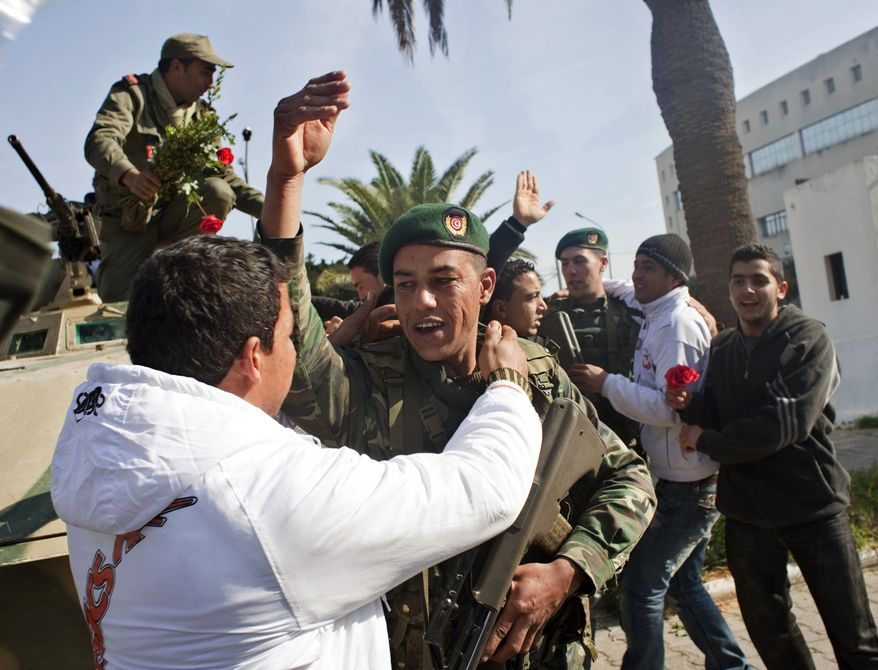 Protesters embrace soldiers during a demonstration against former Tunisian President Zine El Abidine Ben Ali in the center of Tunis, Tunisia, on Monday. Police were seen using tear gas to break up a demonstration on the main avenue in central Tunis on Monday, and helicopters were circling overhead. (Associated Press)