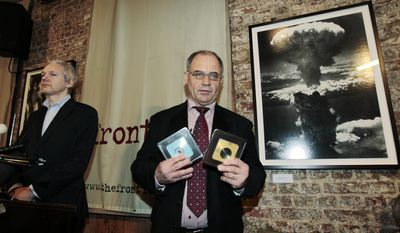 Former Swiss banker Rudolf Elmer poses for the photographers with digital disks he claims have information and documents before handing them to WikiLeaks founder Julian Assange, left, during a press conference at the Frontline Club in London, Monday Jan. 17, 2011. (AP Photo/Lefteris Pitarakis)