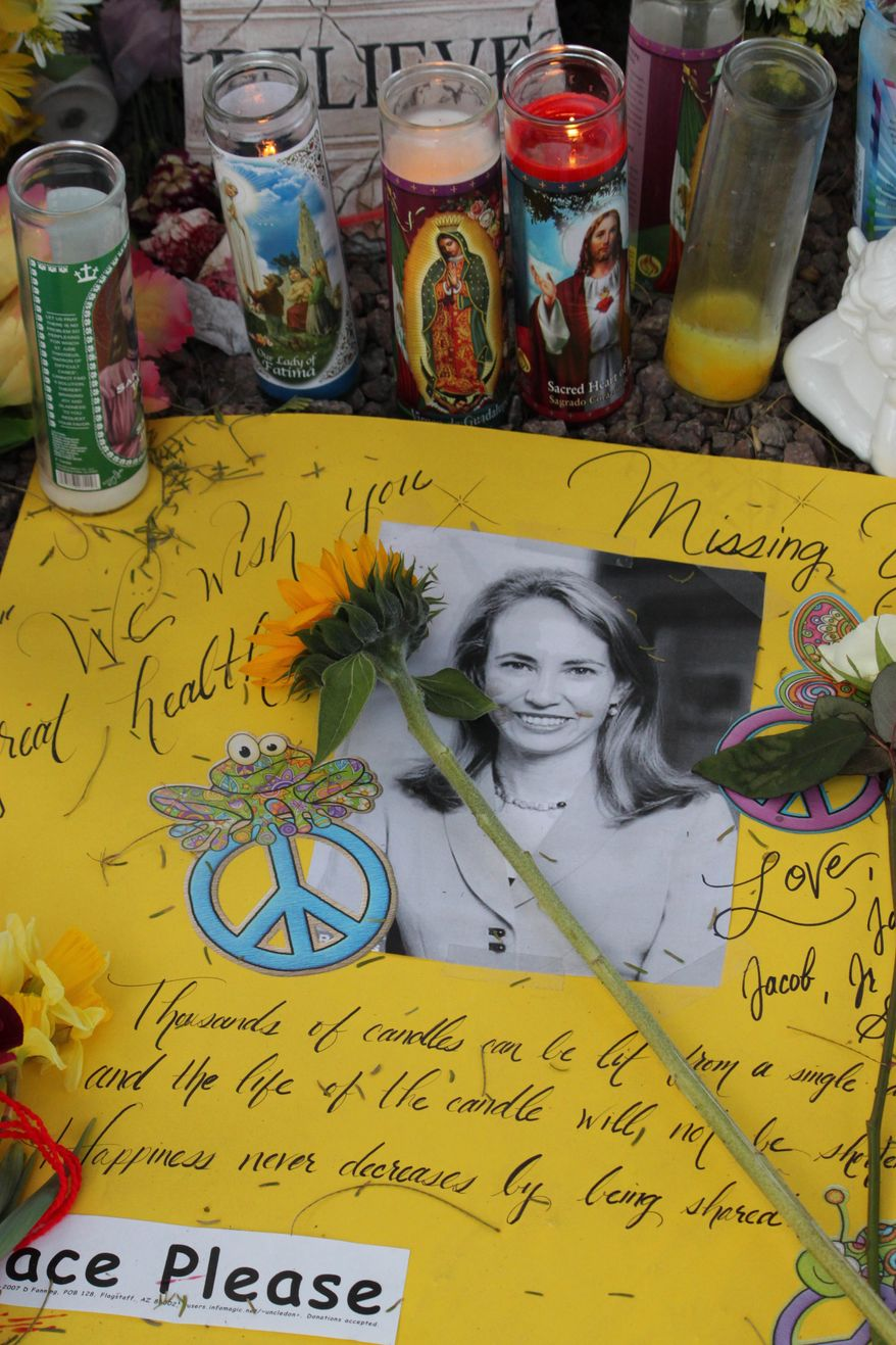 A poster outside of Rep. Gabrielle Giffords office in Tucson, Ariz., wishes her well Sunday, Jan. 16, 2011. Makeshift memorials have sprouted up around Tucson for the victims of the Jan. 8 shooting that killed six people and injured 13, including Giffords. (AP Photo/Susan Montoya Bryan)