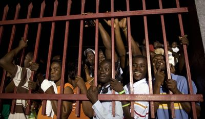 """Supporters of Mr. Duvalier wait outside the terminal of the Toussaint Louverture international airport, after listening to radio reports of his return to Port-au-Prince. """"I'm not here for politics,"""" Mr. Duvalier told Radio Caraibes. """"I'm here for the reconstruction of Haiti."""" (Associated Press)"""