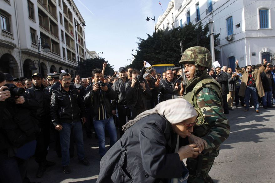 A woman kisses a soldier as she protests against former Tunisian President Zine El Abidine Ben Ali in the center of Tunis, Monday, Jan. 17. 2011. (AP Photo/Christophe Ena)