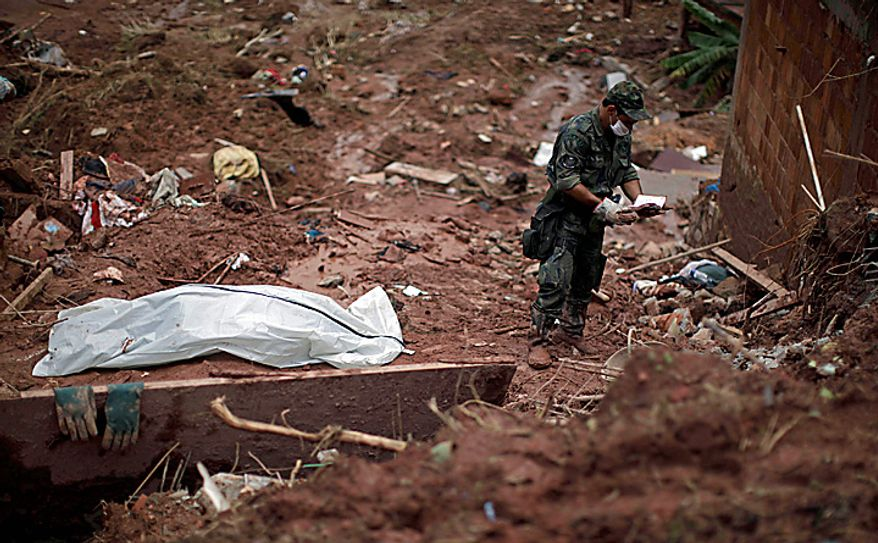 A rescue worker checks a notebook found next to the recovered body of landslide victim Samara Coelho da Silva, 13, left, inside a body bag, in Nova Friburgo, Brazil, Monday, Jan. 17, 2011. Brazil's army on Monday sent 700 soldiers to help throw a lifeline to desperate neighborhoods that have been cut off from food, water or help in recovering bodies since mudslides killed at least 642 people. (AP Photo/Felipe Dana)