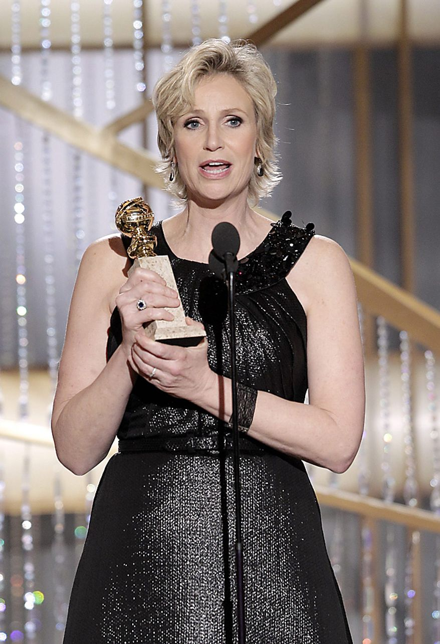 """Actress Jane Lynch holds the award for Best Supporting Actress in a Series/Mini-Series/TV Movie for her role in """"Glee,"""" during the Golden Globe Awards, Sunday, Jan. 16, 2011 in Beverly Hills, Calif. (AP Photo/NBC, Paul Drinkwater)"""