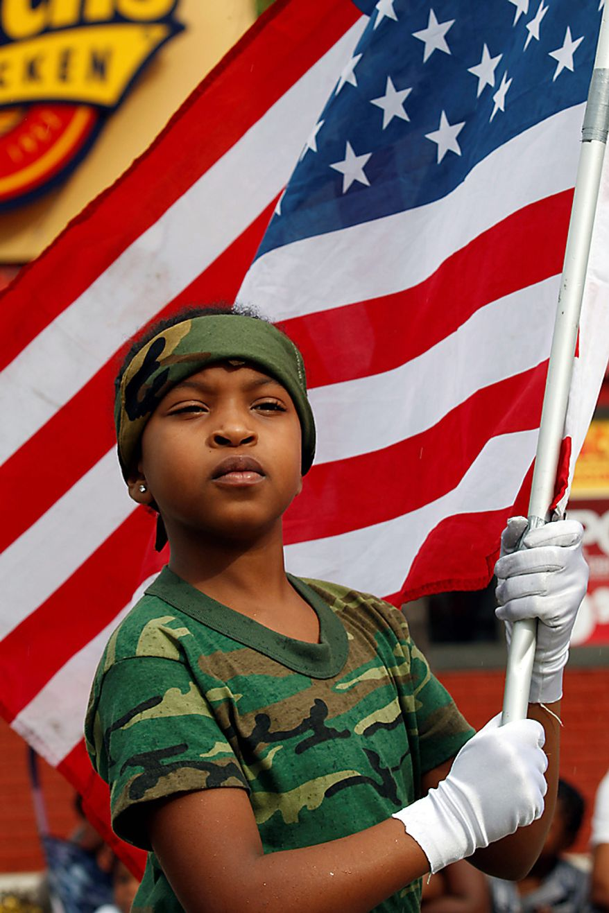 Jahnae Everett, 10, carries the American flag as she and a group of Major Pain's Kids, a program for at-risk youth, prepare to march in a parade honoring the Rev. Martin Luther King Jr. on Monday, Jan. 17, 2011, in the Liberty City neighborhood of Miami. (AP Photo/Wilfredo Lee)