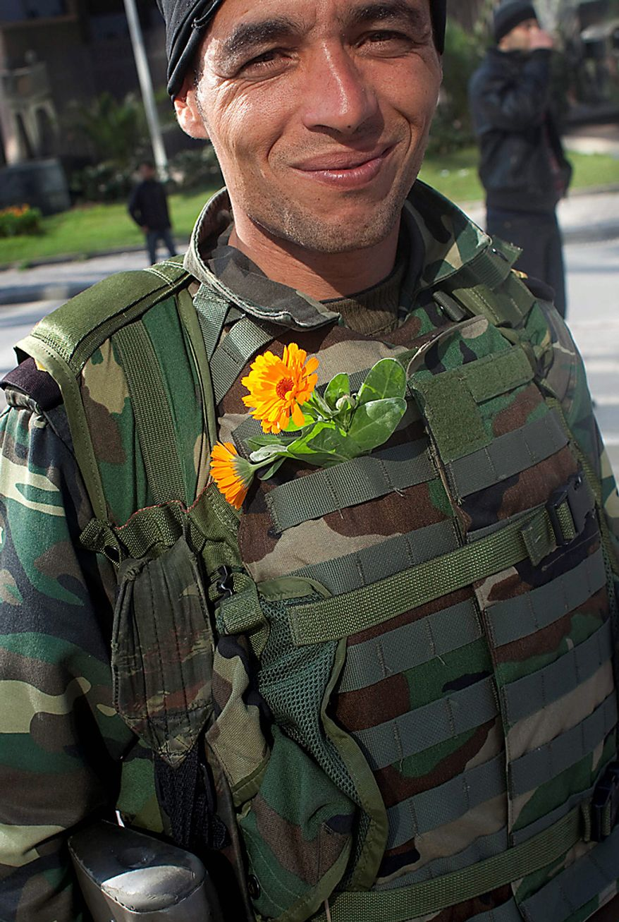 A soldier wears flowers on his uniform during a demonstration against former Tunisian President Zine El Abidine Ben Ali in the center of Tunis, Monday, Jan. 17. 2011. Police were seen using tear gas to break up a demonstration on the main avenue in central Tunis on Monday, and helicopters were circling overhead. (AP Photo/Thibault Camus)