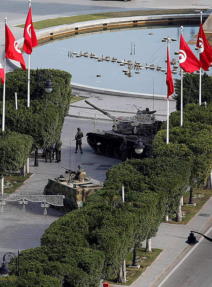 Soldiers stand guard next to their tank in the center of Tunis, Sunday, Jan. 16. 2011. Tunisia sped toward a new future after its iron-fisted leader fled, with an interim president sworn in and ordering the country's first multiparty government to be formed. (AP Photo/Christophe Ena)