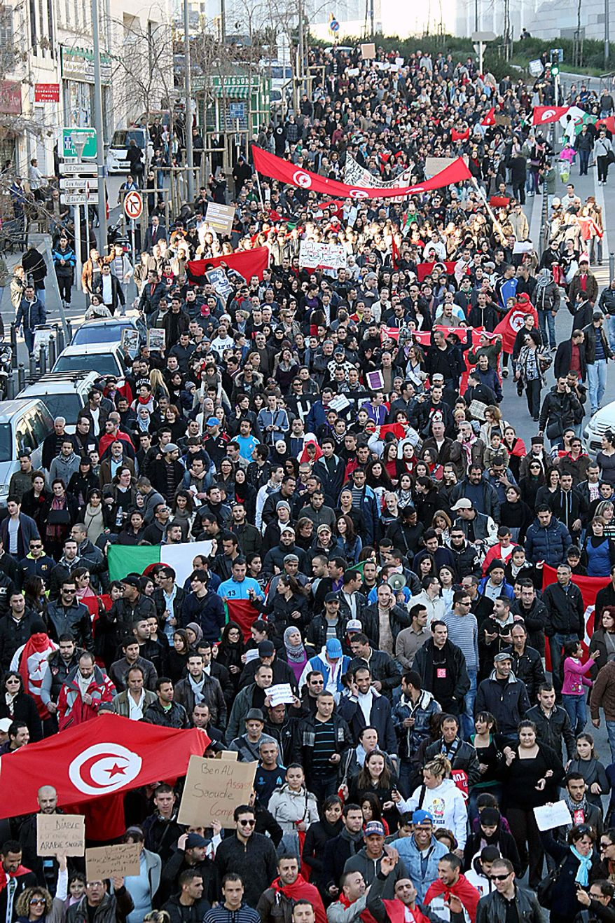 People march during a demonstration in solidarity with Tunisia, in Marseille, southern France , Saturday, Jan. 15, 2011. Unrest engulfed Tunisia on Saturday after a popular rebellion forced the president to flee. Dozens of inmates were killed in two prison fires, looters emptied shops and torched the main train station and gunfire echoed through the capital. (AP Photo/Claude Paris)