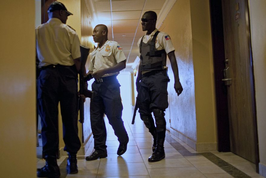 """National police officers patrol a corridor at the hotel floor where Haiti's former dictator Jean-Claude """"Baby Doc"""" Duvalier is staying in Port-au-Prince, Haiti, Tuesday Jan. 18, 2011. (AP Photo/Ramon Espinosa)"""