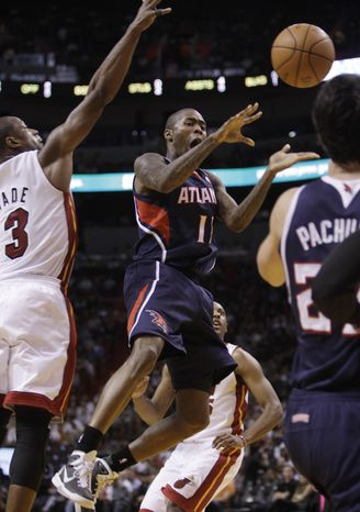 Atlanta Hawks guard Jamal Crawford (11) passes the ball as Miami Heat guard Dwyane Wade (3) defends during the second quarter of the Hawks' 93-89 OT win in Miami on Tuesday. (Associated Press)