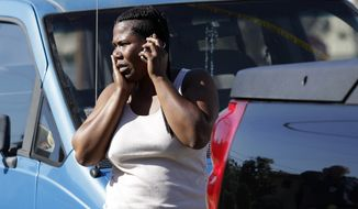 Christy Westbrooks, whose daughter is a junior at Gardena High School, talks on the phone while standing outside the school in Gardena, Calif., on Tuesday. A gun in a 10th-grader's backpack accidentally discharged when he dropped the bag, wounding two students at the school, the campus principal said. (Associated Press)