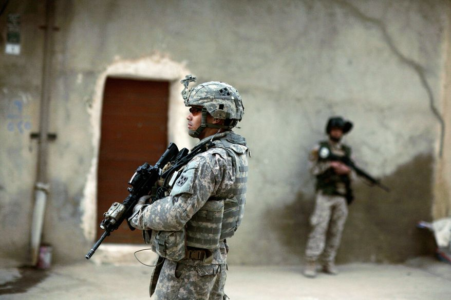 An Iraqi soldier and a U.S. Army soldier (foreground) stand guard during a patrol in Mosul, northwest of Baghdad, in 2009. Two U.S. soldiers were killed Saturday by an Iraqi soldier during a training exercise, raising fresh concerns about Iraq's security forces. (Associated Press)
