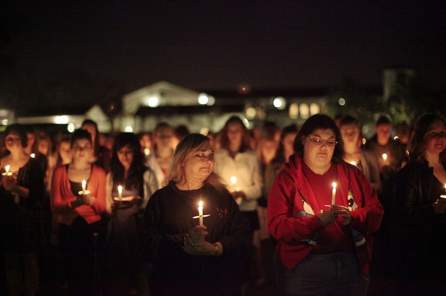Mourners gather at a candlelight vigil honoring Rep. Gabrielle Giffords and other victims of the recent shooting rampage took place in Tucson, Ariz., at Scripps College in Claremont , Calif., Tuesday, Jan. 18, 2011. Mrs. Giffords graduated from Scripps College. (AP Photo/Jae C. Hong)