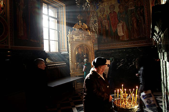 A woman lights prayer candles at the main cathedral in Chisinau, Moldova, during the Epiphany Wednesday Jan. 19, 2011.  The Epiphany, celebrated on January 19, marks the baptism of Jesus in the Orthodox Church and worshippers believe that on