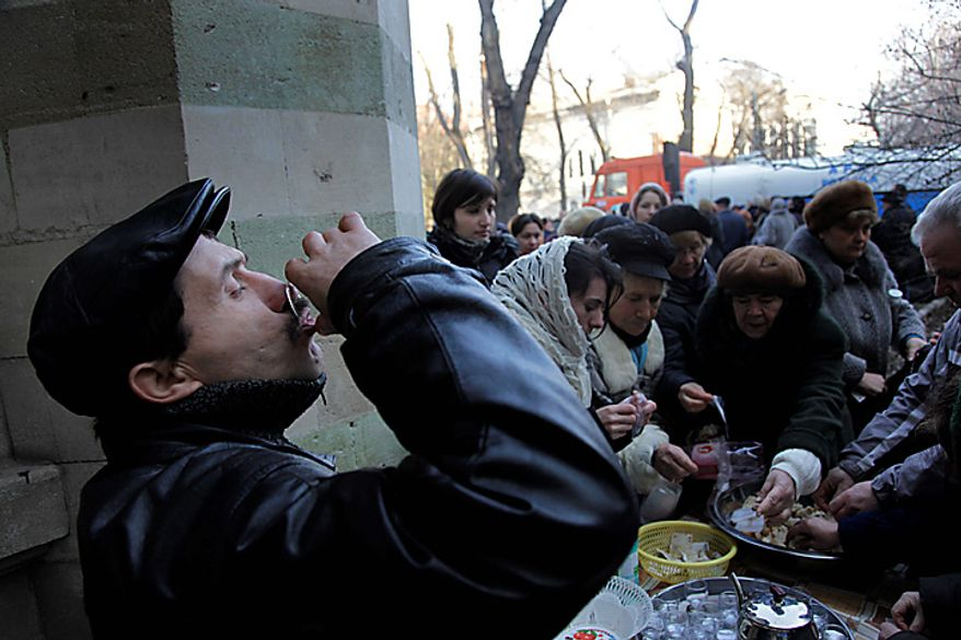 A Moldovan man drinks holy water at a cathedral in Chisinau, Moldova, on Epiphany, Wednesday, Jan. 19, 2011. Epiphany marks the baptism of Jesus in the Orthodox Church, and worshippers believe that on this day water becomes holy and is imbued with special powers. (AP Photo/John McConnico)