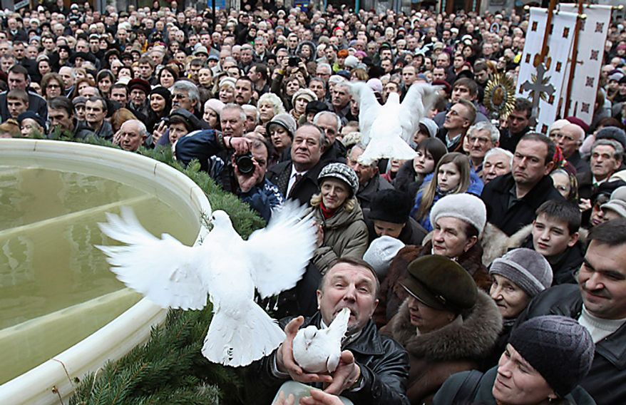 White birds are released over Ukrainian believers during an Epiphany ceremony to bless the water in  Lviv, Ukraine, Wednesday, Jan. 19, 2011. Orthodox believers celebrate the holiday of the Epiphany on Jan. 19, and traditionally bathe in holes cut through thick ice on rivers and ponds to cleanse themselves with water deemed holy for the day. (AP Photo/Petro Zadorozhnyy)