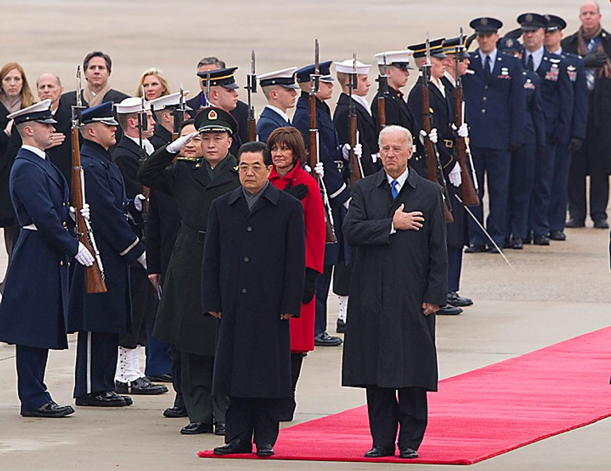 Chinese President Hu Jintao, left, and Vice President Joe Biden stand for the national anthems of both countries during an arrival ceremony on Tuesday, Jan. 18, 2011, at Andrews Air Force Base, Md. (AP Photo/Evan Vucci)