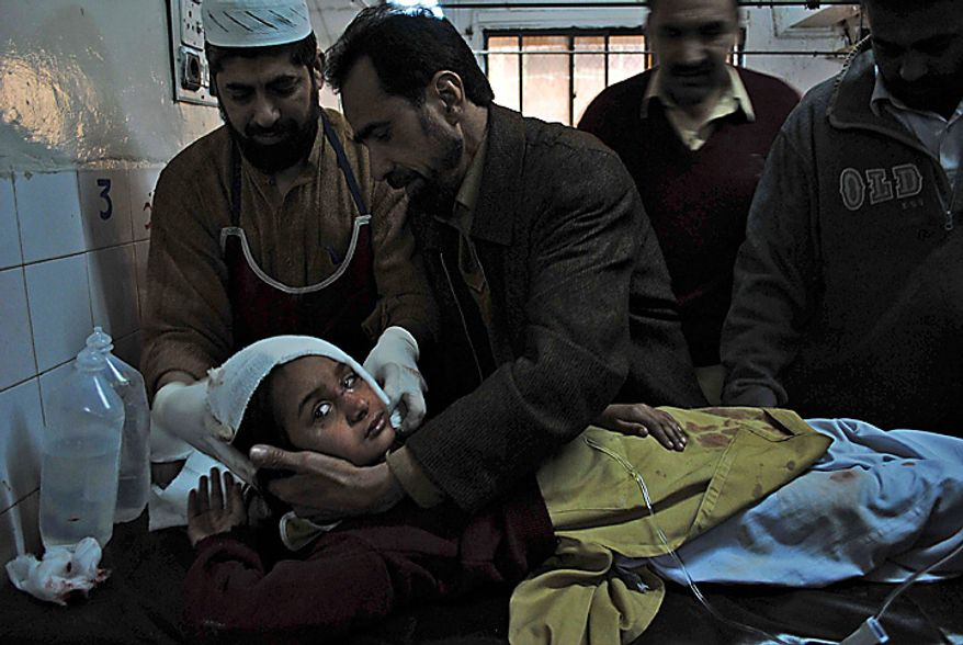 A student injured in a bomb explosion receives treatment at Lady Reading hospital in Peshawar, Pakistan, Wednesday, Jan. 19, 2011. A bomb exploded outside a school in a residential area of Peshawar city on Wednesday, killing at least one person and wounding 14 others. (AP Photo/Mohammad Iqbal)