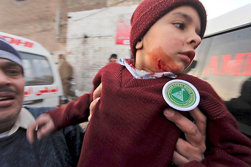 An injured student is rushed to an ambulance at the site of a bomb explosion in Peshawar, Pakistan, Wednesday, Jan. 19, 2011. The bomb exploded outside the school in a residential area of Peshawar city on Wednesday, killing at least one person and wounding 14 others. (AP Photo/Mohammad Sajjad)