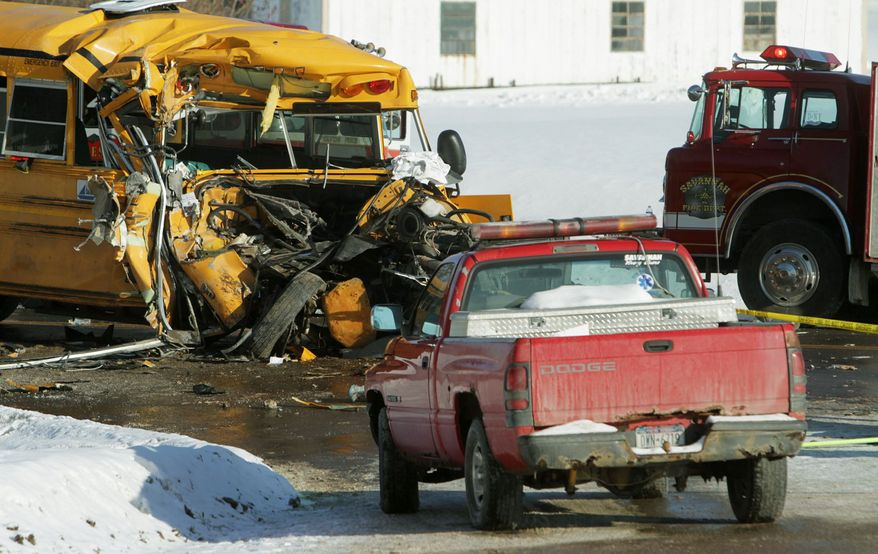 The front end of a school bus sits with its front end crushed after it struck the back of a town snow plow in Savannah, N.Y., on Thursday. Twenty-two children and the driver were injured, authorities said. (Associated Press)