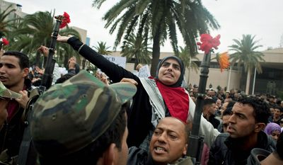 ** FILE ** Armed Tunisian protesters shout slogans against members of the Constitutional Democratic Rally party on Thursday, Jan. 20, 2011, in Tunis, Tunisia. The party was founded by ousted President Zine al-Abidine Ben Ali. (AP Photo)