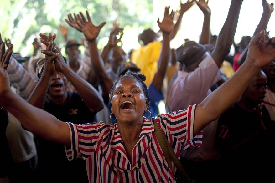 Supporters of Haiti's former dictator Jean-Claude Duvalier chant pro-Duvalier slogans outside the hotel where Mr. Duvalier is staying in Port-au-Prince, Haiti, Wednesday Jan. 19, 2011. (AP Photo/Rodrigo Abd)
