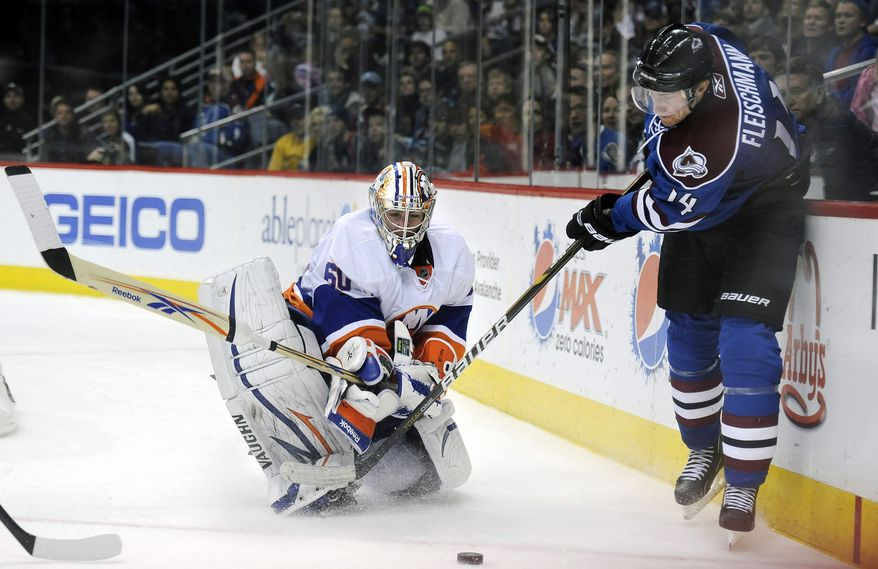 Colorado Avalanche left wing Tomas Fleischmann, of the Czech Republic, tries to flip the puck past New York Islanders goalie Kevin Poulin in the second period of an NHL hockey game in Denver, Colo., on Saturday, Jan. 8, 2011. The Islanders won 4-3 in overtime. (AP Photo/Chris Schneider)