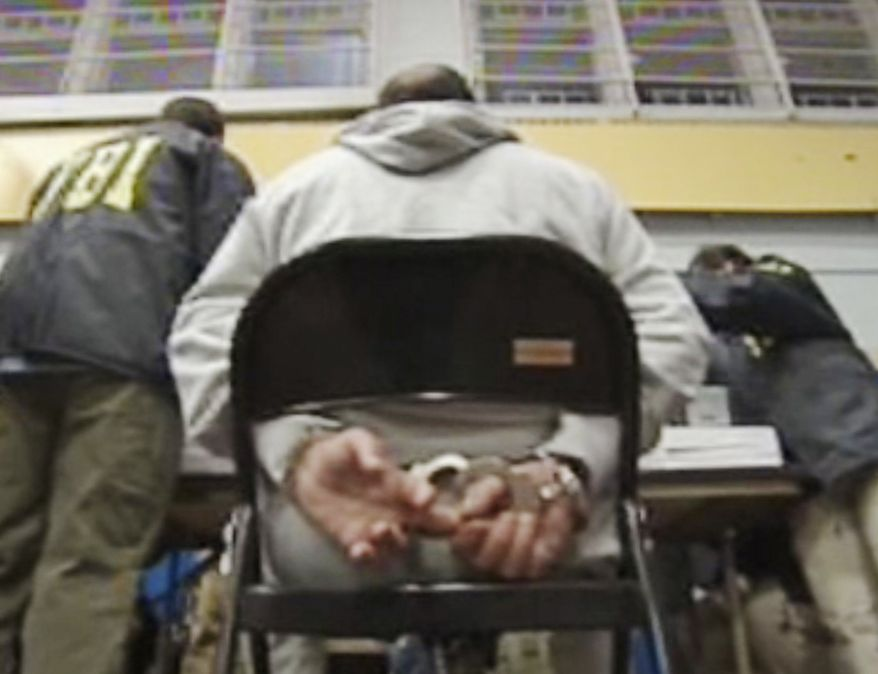 In this frame grab taken from Associated Press Television News video, a suspect sits handcuffed Thursday, Jan. 20, 2011, in the Brooklyn borough of New York. Federal agents dealt another major blow to New York's five Mafia crime families by arresting more than 100 suspected mobsters throughout the Northeast on charges including murder, extortion and narcotics trafficking. (AP Photo/APTN, Pool)