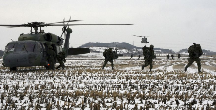 In this photo released by the South Korean Army via Yonhap, South Korean Army soldiers run out from a Black Hawk helicopter during an exercise to prepare for possible aggression by North Korea in Jindo, south of Seoul, South Korea, Thursday, Jan. 20, 2011. South Korea has welcomed an agreement between leaders of the United States and China on the need to maintain peace and stability on the Korean Peninsula and achieve its denuclearization. (AP Photo/South Korean Army via Yonhap)