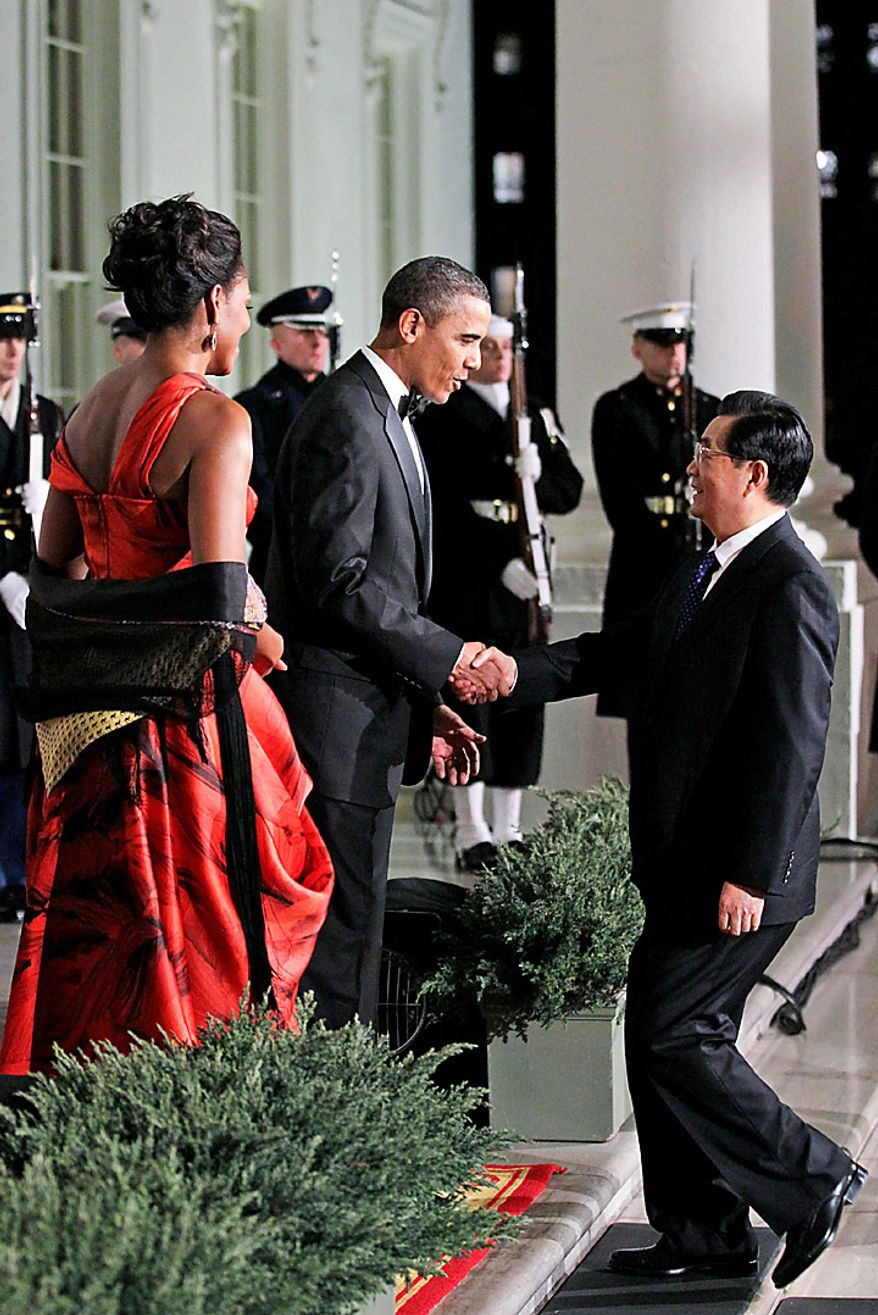 President Barack Obama and first lady Michelle Obama welcome China's President Hu Jintao to the North Portico of the White House in Washington, Wednesday, Jan. 19, 2011, for the State Dinner. (AP Photo/Carolyn Kaster)